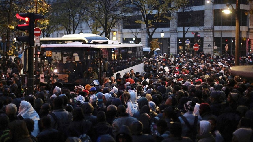 Migrants wait to board buses to temporary shelters, in Paris, Friday, Nov. 4, 2016. Police and city officials are clearing out hundreds of migrants camped out on sidewalks in northern Paris in a camp that recently grew into a new challenge for the French government. (AP Photo/Thibault Camus)