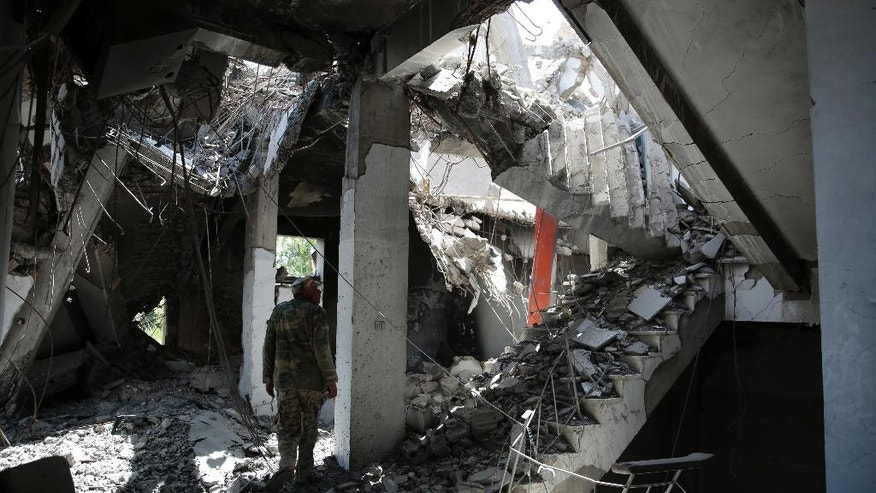 In this Oct. 9, 2016 photo, a Yemeni soldier walks amid the rubble of a Government compound building that was destroyed by Saudi-led airstrikes, in Saada province, northwest of Sanaa, Yemen. Saada, the main stronghold of Yemen's Houthi rebels, has been one of the most densely bombed cities in the country during the 19-month air campaign by Saudi Arabia and its allies. Over the past year, an estimated 40 percent of its 50,000 residents fled. Many of those who remained literally dug holes in the ground to hide in and moved schools and hospitals into caves for protection. But some of those who fled have started filtering back. (AP Photo/Hani Mohammed)