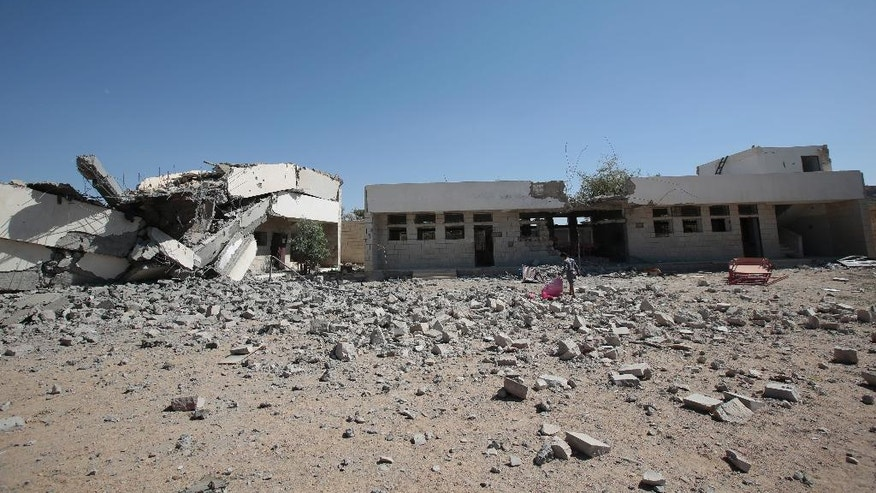 In this Oct. 9, 2016 photo, a Yemeni boy walks amid the rubble of a damaged school by Saudi-led airstrikes in Saada province, northwest of Sanaa, Yemen. Saada, the main stronghold of Yemen's Houthi rebels, has been one of the most densely bombed cities in the country during the 19-month air campaign by Saudi Arabia and its allies. Over the past year, an estimated 40 percent of its 50,000 residents fled. Many of those who remained literally dug holes in the ground to hide in and moved schools and hospitals into caves for protection. But some of those who fled have started filtering back. (AP Photo/Hani Mohammed)