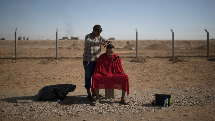 A displaced man has his hair cut at Jedaa camp in Qayara, south of Mosul, Iraq, Thursday, Nov. 3, 2016. A senior military commander says more than 5,000 civilians have been evacuated from newly-retaken eastern parts of the Islamic State group-held city of Mosul and taken to camps. (AP Photo/Felipe Dana)