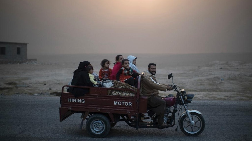 A displaced Iraqi family rides back to their home at the outskirts of Qayara, south of Mosul, Iraq, Thursday, Nov. 3, 2016. A senior military commander says more than 5,000 civilians have been evacuated from newly-retaken eastern parts of the Islamic State group-held city of Mosul and taken to camps. (AP Photo/Felipe Dana)