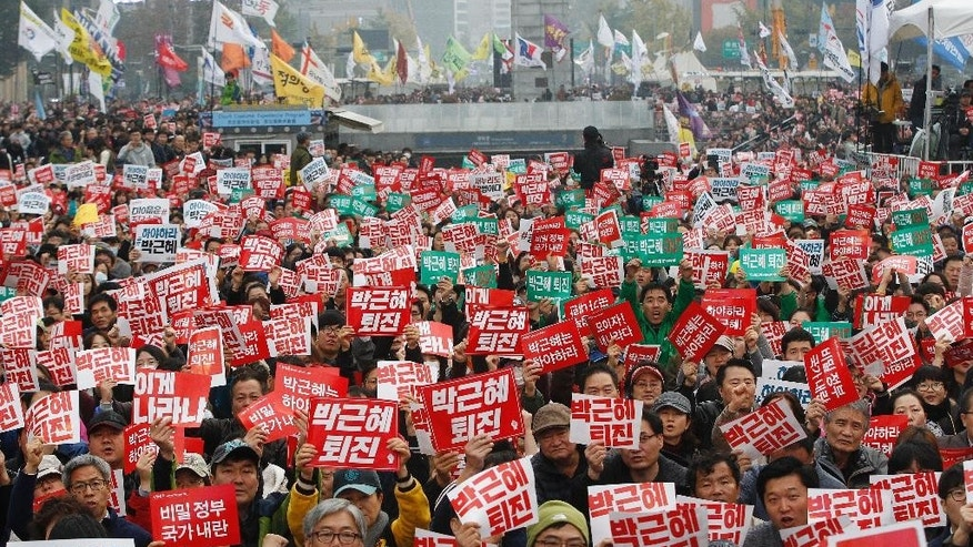 "South Korean protesters stage a rally calling for South Korean President Park Geun-hye to step down in downtown Seoul, South Korea, Saturday, Nov. 5, 2016. Tens of thousands of South Koreans are expected to march in Seoul to demand Park's resignation on Saturday, a day after she took blame for a ""heartbreaking"" scandal and rising suspicion that she allowed a mysterious confidante to manipulate power from the shadows. The signs read ""Park Geun-hye should step down."" (AP Photo/Ahn Young-joon)"