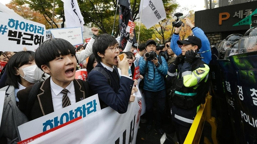 "South Korean high school students are blocked by police officers as they march toward the presidential house after a rally calling for South Korean President Park Geun-hye to step down in downtown Seoul, South Korea, Saturday, Nov. 5, 2016. Tens of thousands of South Koreans are expected to march in Seoul to demand Park's resignation on Saturday, a day after she took blame for a ""heartbreaking"" scandal and rising suspicion that she allowed a mysterious confidante to manipulate power from the shadows. The signs read ""Park Geun-hye should step down."" (AP Photo/Ahn Young-joon)"
