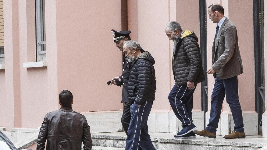 The two Italian hostages that were freed in Libya, Bruno Cacace, second from left, and Danilo Calonego, second from right, leave a police station after being questioned by prosecutor Sergio Colaiocco, in Rome, Saturday, Nov. 5, 2016. The two had been kidnapped at Gath, Libya, on Sept. 19.  (Giuseppe Lami/ANSA via AP)