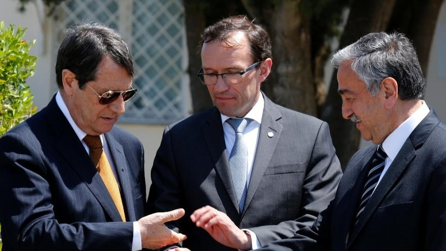 FILE - In this Friday, May 15, 2015 file photo, Cyprus President Nicos Anastasiades, left, Turkish Cypriot leader Mustafa Akinci, right, and United Nations envoy Espen Barth Eide symbolically join hands after their talks at a UN compound in the Cypriot divided capital Nicosia, Cyprus.  Past efforts to solve the ethnical division of Cyprus have failed, but details are revealed Saturday Nov. 5, 2016, the leaders are heading to the Swiss resort of Mont Pelerin for meetings next week that could be the precursor to one last summit to sort out the final details of a deal. (AP Photo/Petros Karadjias, FILE)