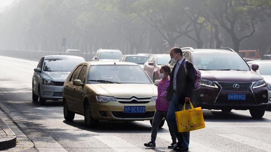 A man and a child wear masks during a heavily polluted day in Beijing, China, Saturday, Nov. 5, 2016. China's cabinet has issued a new climate plan targeting an 18-percent cut in carbon emissions by 2020 compared to 2015 levels. (AP Photo/Ng Han Guan)