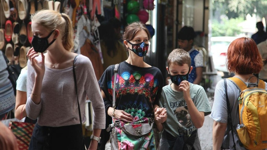 Foreigners walk at a market place wearing face masks against air pollution in New Delhi, India, Friday, Nov. 4, 2016. A new report from UNICEF says about a third of the 2 billion children in the world who are breathing toxic air live in northern India and neighboring countries, risking serious health effects including damage to their lungs, brains and other organs. New Delhi's air pollution is among the world's worst, spikes every winter because of the season's weak winds and countless garbage fires. (AP Photo/Altaf Qadri)