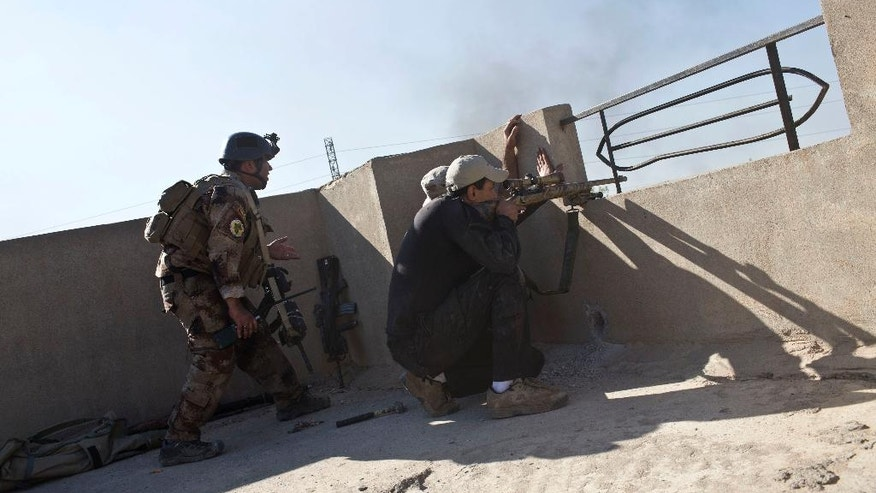 Iraqi special forces soldiers fire at Islamic State positions on the outskirts of Mosul, Iraq, Friday, Nov. 4, 2016. Heavy fighting erupted in the eastern neighborhoods of Mosul on Friday as Iraqi special forces launched an assault deeper into the urban areas of the city and swung round to attack Islamic State militants from a second entry point, to the northeast. (AP Photo/Marko Drobnjakovic)