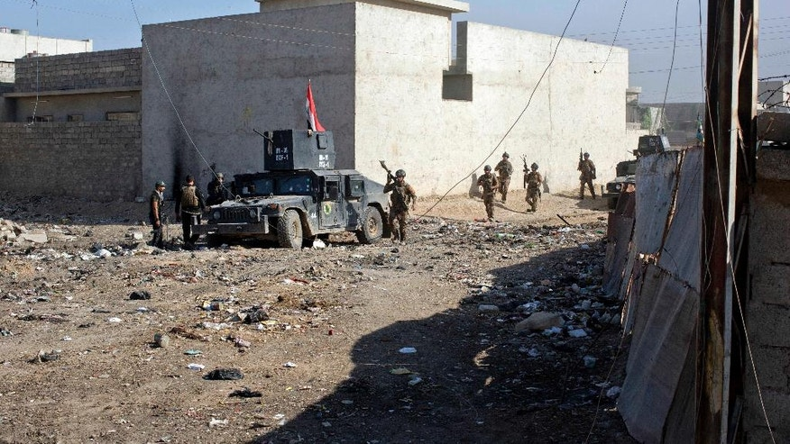 Iraqi special forces soldiers move on foot through an alley on the outskirts of Mosul, Iraq, Friday, Nov. 4, 2016. Heavy fighting erupted in the eastern neighborhoods of Mosul on Friday as Iraqi special forces launched an assault deeper into the urban areas of the city and swung round to attack Islamic State militants from a second entry point, to the northeast. (AP Photo/Marko Drobnjakovic)
