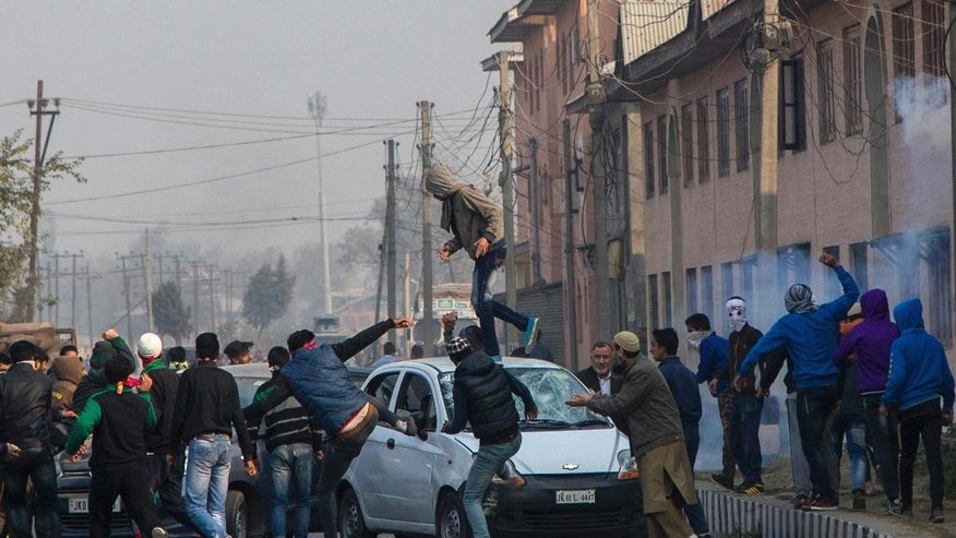 Kashmiri protesters smash windshields of private cars for ignoring separatist-sponsored strike during the funeral of Qaiser Sofi in Srinagar, Indian controlled Kashmir, Saturday, Nov. 5, 2016. Police in Indian-controlled Kashmir say at least 30 people were injured after government forces fired shotgun pellets and tear gas as a funeral procession for a teenager turned into a protest.(AP Photo/Dar Yasin)