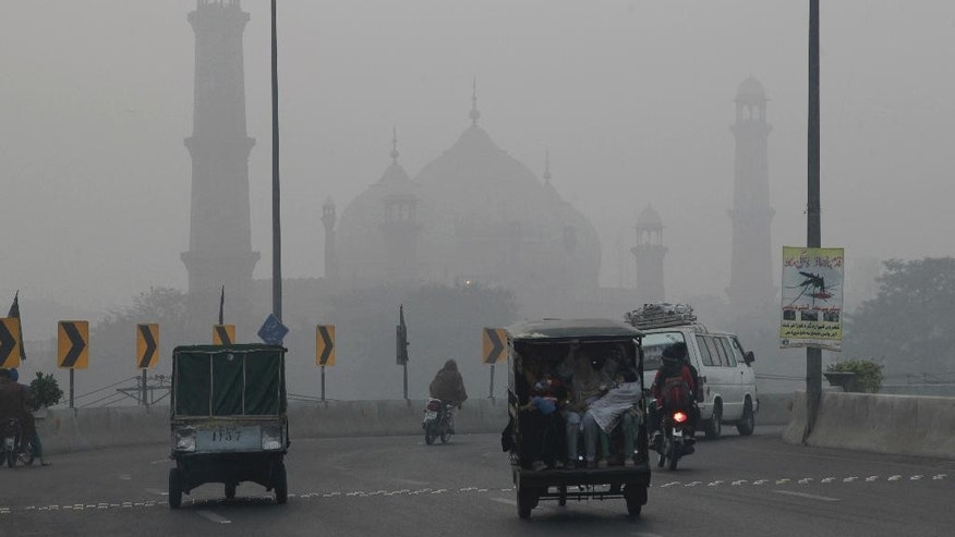 Motorists drive through a road close to historical Badshahi mosque while dense smog engulf the neighborhood of Lahore, Pakistan, Saturday, Nov. 5, 2016. Thick smog has engulfed several cities in central Pakistan for a few days, causing, breathing problems, road accidents and disruption of flight and train scheduled as well as the closure of the sections of the main motorways. (AP Photo/K.M. Chaudary)