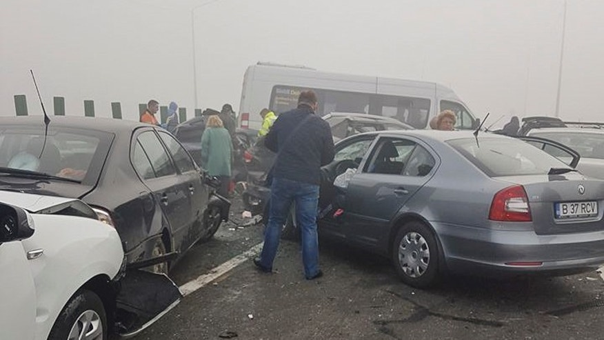People survey damage at the scene of a multi-vehicle accident on the A2 highway, some 40 Km (25 miles) east of Bucharest, Romania, Saturday, Nov. 5, 2016.  Authorities say at least 3 died and dozens more were injured in the pileup on a highway in foggy weather. (AP Photo/Florin Vladescu)