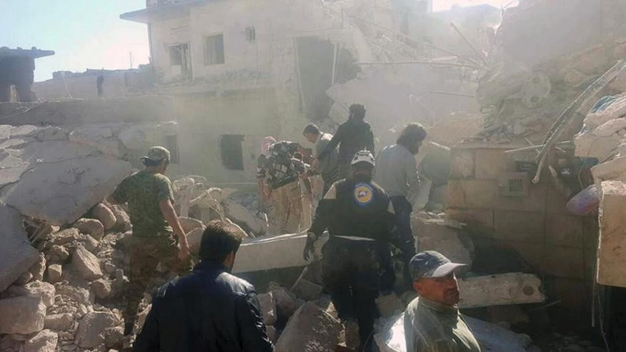 This photo provided by the Syrian Civil Defense White Helmets, which has been authenticated based on its contents and other AP reporting, shows Civil Defense workers and Syrian citizens inspecting damaged buildings after airstrikes hit in Darat Izza town, in rural western Aleppo province, Syria, Saturday, Nov. 5, 2016. Despite a halt in airstrikes in eastern Aleppo city, there has been an intense aerial bombing campaign in the western Aleppo countryside and nearby Idlib province. Rebels say the strikes are an attempt to sever the supply lines of the rebels, waging an offensive on government-held western Aleppo. (Syrian Civil Defense White Helmets via AP)