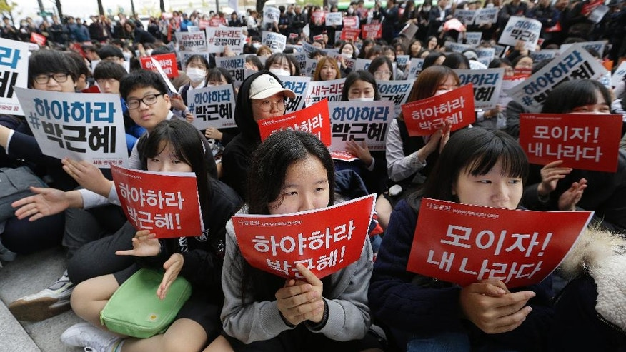 "South Korean high school students stage a rally calling for South Korean President Park Geun-hye to step down in downtown Seoul, South Korea, Saturday, Nov. 5, 2016. Tens of thousands of South Koreans are expected to march in Seoul to demand President Park Geun-hye's resignation on Saturday, a day after she took blame for a ""heartbreaking"" scandal and rising suspicion that she allowed a mysterious confidante to manipulate power from the shadows. The letters read ""Park Geun-hye should step down."" (AP Photo/Ahn Young-joon)"