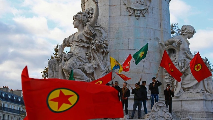 Kurdish supporters who live in France, chant slogans and display Kurdisk flags during a rally to protest against Turkish President Recep Tayyip Erdogan, at Republique Square in Paris, Saturday, Nov. 5, 2016. Authorities in Turkey detained 11 pro-Kurdish lawmakers early Friday as part of ongoing terror-related investigations, including both party co-chairs Selahattin Demirtas and Figen Yuksekdag and other senior officials, the Interior Ministry said. (AP Photo/Francois Mori)