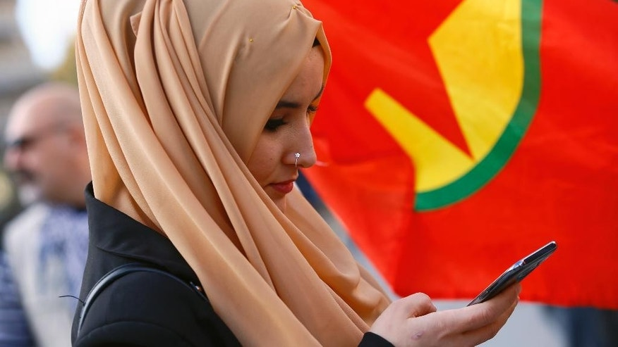 A Kurdish woman sends photos with her phone during a rally to protest against Turkish President Recep Tayyip Erdogan, at Republique Square in Paris, Saturday, Nov. 5, 2016. Authorities in Turkey detained 11 pro-Kurdish Peoples' Democratic Party (HDP) lawmakers early Friday as part of ongoing terror-related investigations, including both party co-chairs Selahattin Demirtas and Figen Yuksekdag and other senior officials, the Interior Ministry said. (AP Photo/Francois Mori)