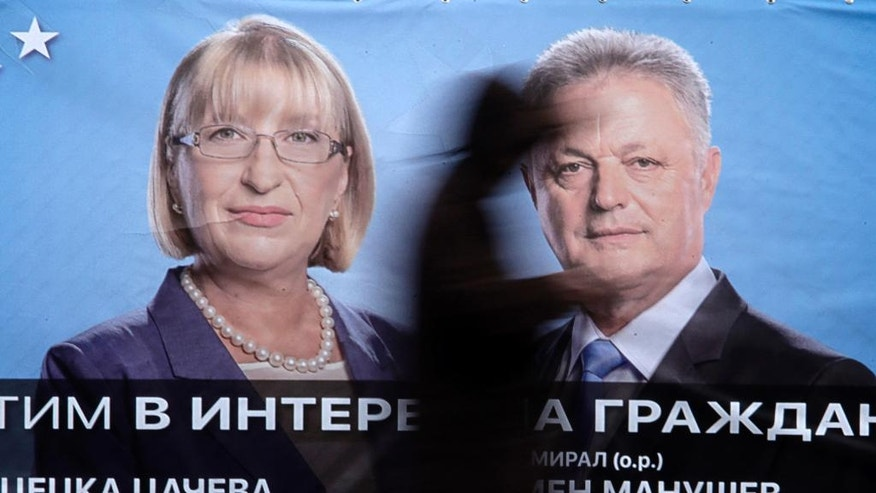 A man passes in front pre-election poster of Bulgaria's centre-right ruling GERB party presidential candidate Tsetska Tsacheva and vice-president Plamen Manushev, right, in Sofia, Friday, Nov. 4, 2016. Bulgarians will to choose their new president on Sunday to replace incumbent Rosen Plevneliev after his five-year term ends next January. The election campaign focused mainly on the future of the European Union, relations with Russia and the threats from a possible rise in migrant inflows from neighboring Turkey(AP Photo/Valentina Petrova)