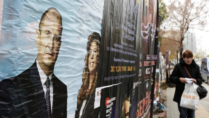 A woman passes near pre-election posters of Bulgaria's Socialist party presidential candidate Rumen Radev and vice-president Iliana Yotova, right, in Sofia, Friday, Nov. 4, 2016. Bulgarians will to choose their new president on Sunday to replace incumbent Rosen Plevneliev after his five-year term ends next January. The election campaign focused mainly on the future of the European Union, relations with Russia and the threats from a possible rise in migrant inflows from neighboring Turkey. (AP Photo/Valentina Petrova)