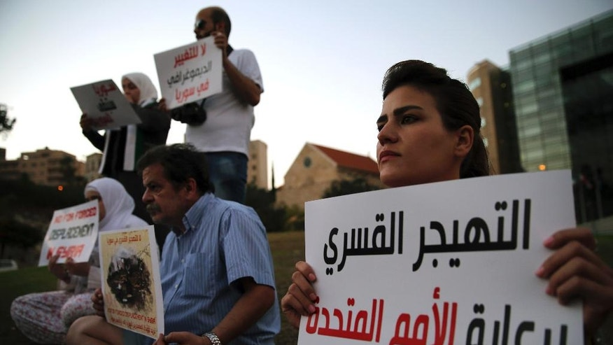 "In this picture taken on Friday, Oct. 7, 2016, Syrian citizens attend a sit-in against the forced displacement in Syria, in front the United Nations headquarters, in downtown Beirut, Lebanon. Syrian opposition figures and refugees point to an array of obstacles facing the displaced who want to return home, saying that the government is machinating to discourage potentially restive populations from returning to areas they fled during the war. The Arabic placard reads:""The forced displacement sponsored by the United Nations."" (AP Photo/Hussein Malla)"