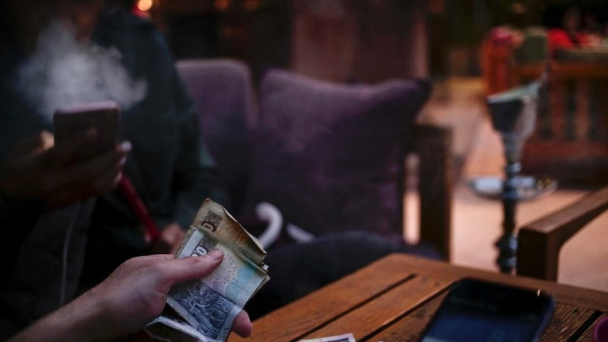 FILE - In this Saturday, Oct. 22, 2016 file photo, a man pays his bill as his friend smokes a waterpipe, or shisha, at a cafe in Cairo, Egypt. The Egyptian pound is trading in banks at around 16 to the dollar, down from the 13-pound peg the Central Bank set as a guiding exchange rate when it floated the currency last week. Banks were selling the U.S. currency at 16 pounds while buying it at around 15.5 pounds on Sunday, the first full business day in Egypt since the Central Bank floated the currency on Thursday. (AP Photo/Nariman El-Mofty, File)