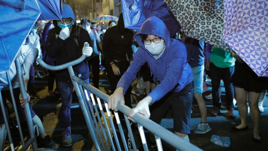 Protesters try to set up barriers against police officers outside the Chinese central government's liaison office in Hong Kong, Sunday, Nov. 6, 2016. Thousands of protesters marched in Hong Kong on Sunday, demanding that China's central government stay out of a political dispute in the southern Chinese city after Beijing indicated that it would intervene to deter pro-independence advocates. (AP Photo/Vincent Yu)