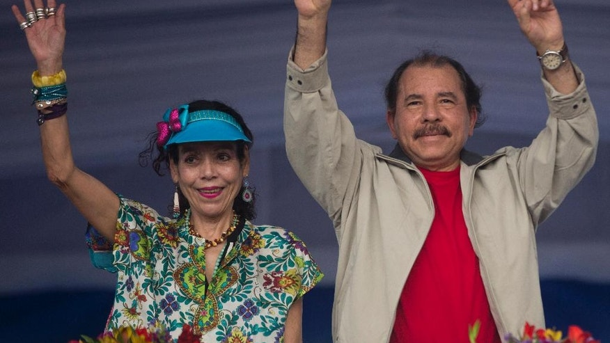 FILE.- In this July 3, 2016 file photo Nicaragua's President Daniel Ortega, right, and first lady Rosario Murillo, wave to supporters during an event commemorating the 36th anniversary of the Sandinista National Liberation Front withdrawal to Masaya, in Managua, Nicaragua. Murillo now running as her husband's VP ticket mate in a Nov. 6 election seen as a shoo-in and is poised to finally have the title to match her true influence. (AP Photo/Esteban Felix, File)