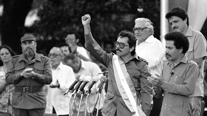 FILE - In this Jan. 10, 1985 file photo, Nicaraguan President Daniel Ortega raises his fist after being sworn in as the countries new president, in Managua, Nicaragua. Ortega, who helped topple the dictatorship of Anastasio Somoza as a Sandinista guerrilla leader, ruled Nicaragua from 1979-1990. After losing power in a shock electoral defeat, he later returned to power through the ballot box, assuming the presidency again in 2007. Fidel Castro is pictured left. (AP Photo/Jeff Robbins, File)