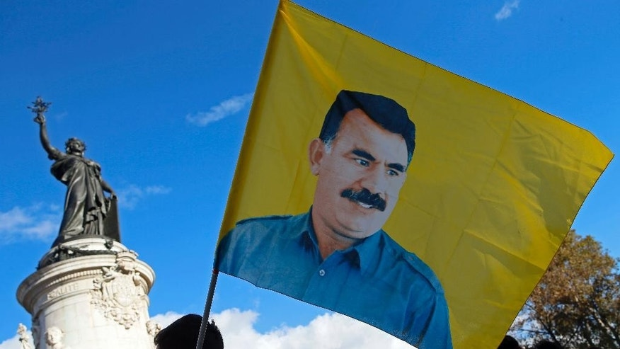 A Kurdish demonstrator holds a flag featuring kurdish PKK leader Abdullah Ocalan during a rally to protest against Turkish President Recep Tayyip Erdogan, at Republique Square in Paris, Saturday, Nov. 5, 2016Authorities in Turkey detained 11 pro-Kurdish Peoples' Democratic Party (HDP) lawmakers early Friday as part of ongoing terror-related investigations, including both party co-chairs Selahattin Demirtas and Figen Yuksekdag and other senior officials, the Interior Ministry said. (AP Photo/Francois Mori)