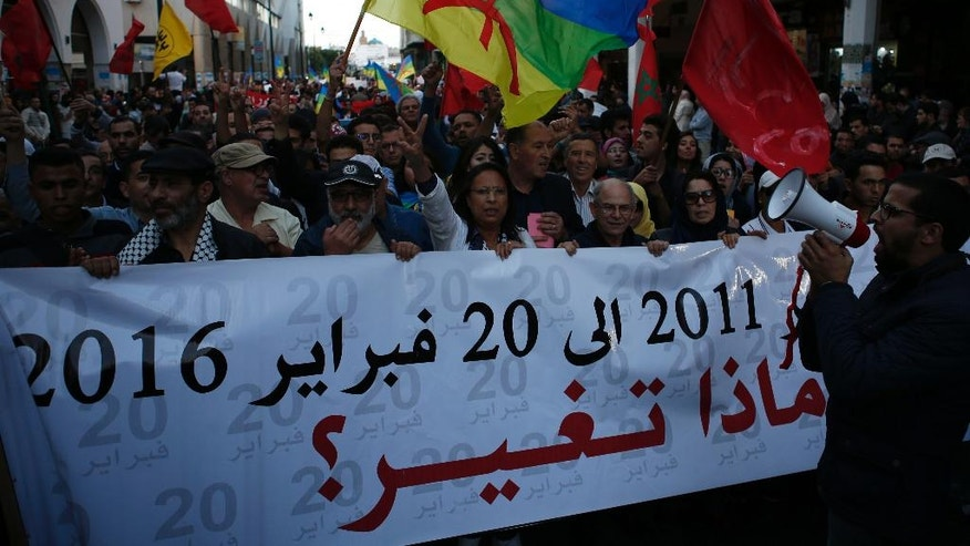 """People hold Amazigh flags and Moroccan flags in Rabat, Morocco, Friday Nov. 6, 2016, and mark a week after the death of fish vendor Mouhcine Fikri, who was crushed in a garbage truck. Protests have been taking place in Morocco since last Friday. Banner reads """"from 20 February 2011 to 20 February 2016 Nothing has Changed"""". (AP Photo/Abdeljalil Bounhar)"""