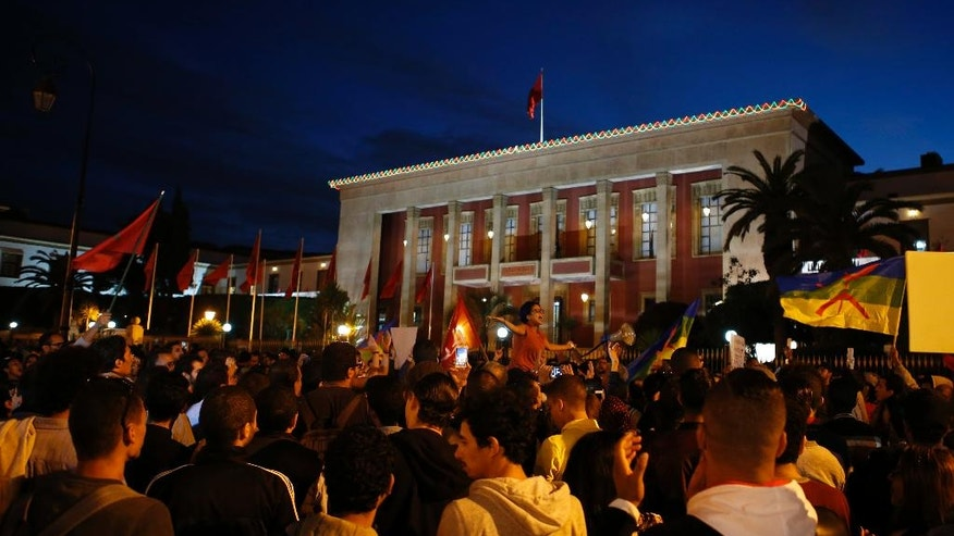 People stand outside the Moroccan parliament building in Rabat, Morocco, Sunday Nov. 6, 2016, to mark a week after the death of fish vendor Mouhcine Fikri, who was crushed in a garbage truck. Protests have been taking place in Morocco since last Friday. (AP Photo/Abdeljalil Bounhar)