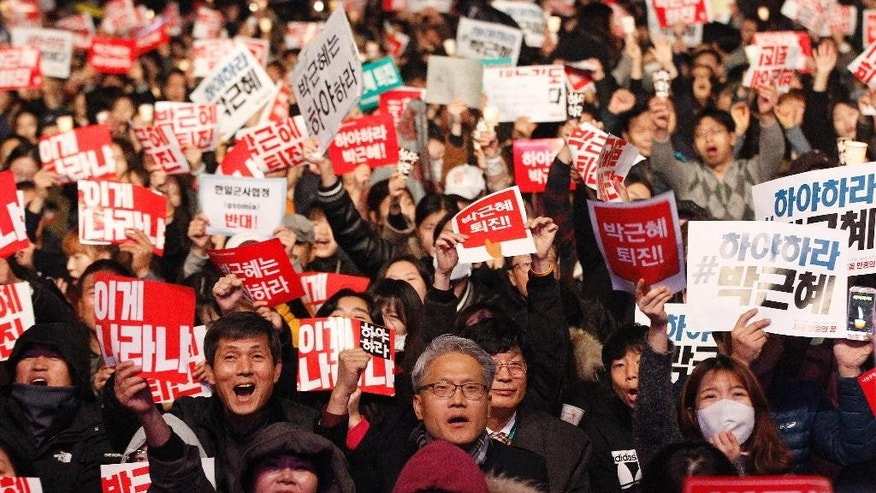 FILE - In this Saturday, Nov. 5, 2016, file photo, South Korean protesters shout slogans during a rally calling for South Korean President Park Geun-hye to step down in downtown Seoul, South Korea. In only a few days, South Korea's biggest scandal in years has done what six decades of diplomacy and bloodshed couldn't, uniting the rival Koreas, at least in one area: indignation against South Korea's leader. North Korean propaganda regularly attacks South Korean President Park Geun-hye. Many South Koreans now seem to be reaching Pyongyang levels of fury over an investigation into whether Park allowed a longtime confidante to manipulate her administration from the shadows. (AP Photo/Ahn Young-joon, File)