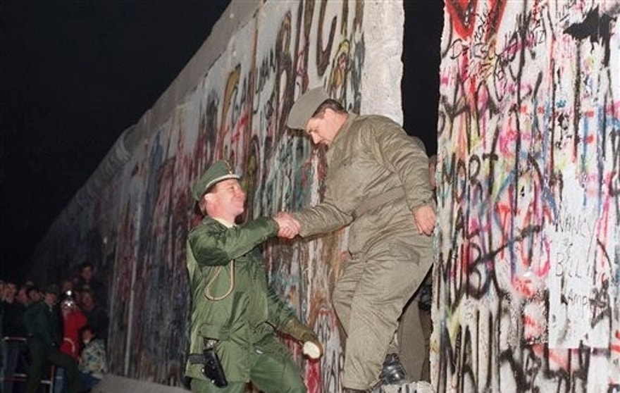 A West German policeman, left, gives a helping hand to an East German border guard who climbs through a gap of the Berlin Wall when East Germany opened another passage at Potsdamer Platz in Berlin, Nov. 12, 1989. (AP Photo/Thomas Kienzle)
