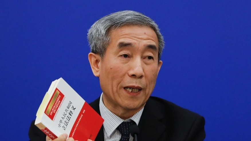 Li Fei, deputy secretary general of the National People's Congress Standing Committee, holds a China's legislation law book while speaking during a press conference at the Great Hall of the People in Beijing, Monday, Nov. 7, 2016. China's top legislature effectively barred two democratically elected separatist lawmakers from taking office in Hong Kong with a ruling Monday on the city's constitution, an intervention into a local political dispute that's likely to spark further turmoil in the southern Chinese city. (AP Photo/Andy Wong)