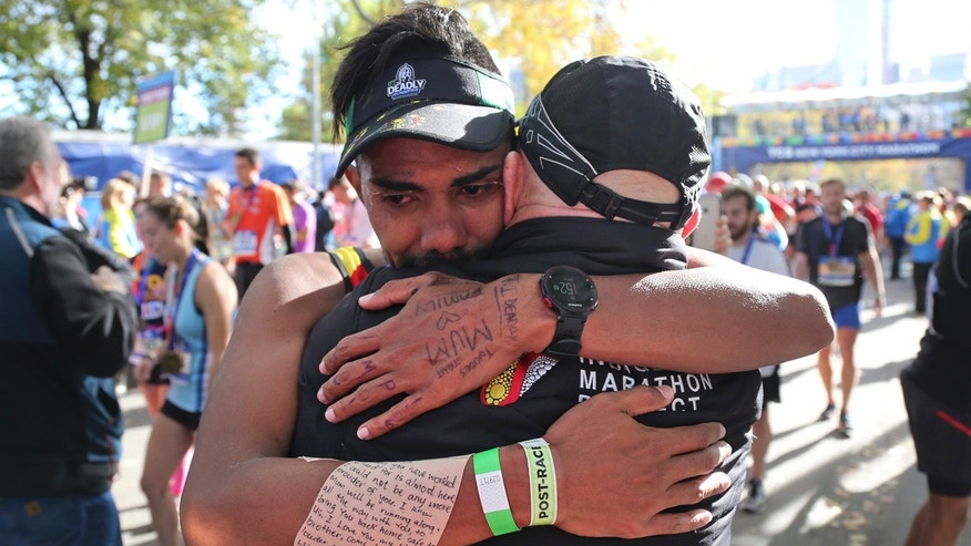 Saliman Binjuda of Thursday Island, Australia, hugs Robert de Castella, founder of the Indigenous Marathon Foundation, at the finish line of the 2016 New York City Marathon in New York, Sunday, Nov. 6, 2016.