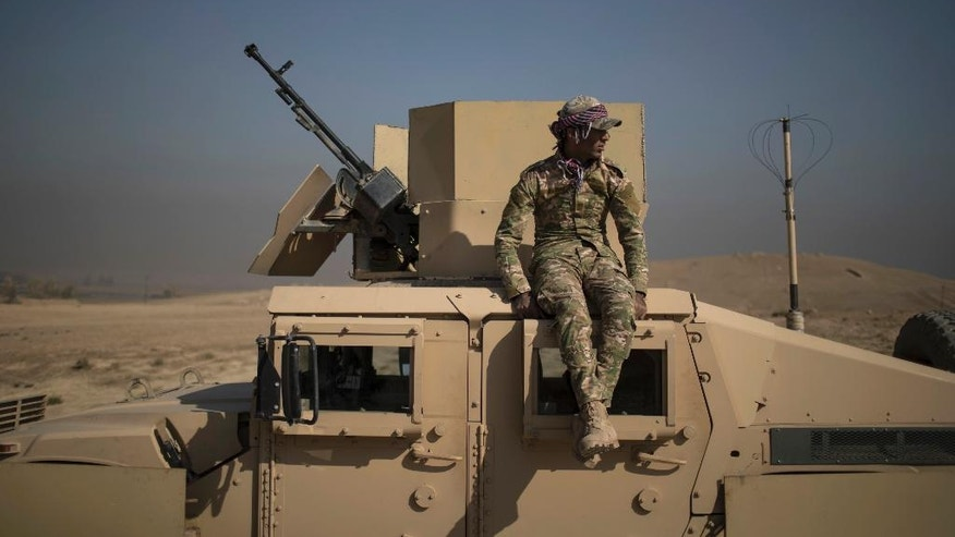 An Iraqi army soldier sits atop an armored vehicle on the outskirts of Hamam al-Alil, south of Mosul, Iraq, Sunday, Nov. 6, 2016. On the southern front, Iraqi forces are still some 12 miles (20 kilometers) from the city center. The fighting is centered on the town of Hamam al-Alil, where Associated Press journalists could hear gunfire and saw attack helicopters firing on IS positions. (AP Photo/Felipe Dana)