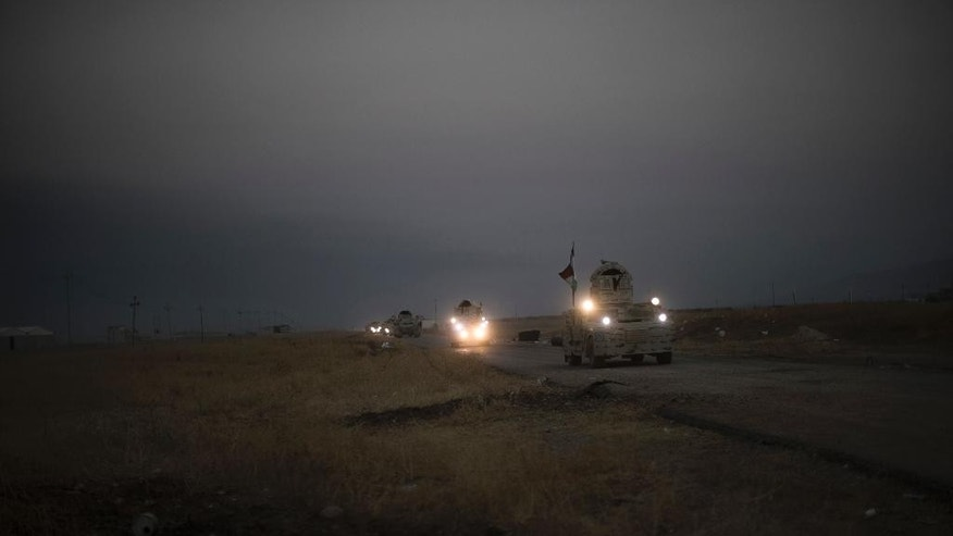 Kurdish Peshmerga convoy drives towards a frontline in Bashiqa, east of Mosul, Iraq, Monday, Nov. 7, 2016. Iraqi Kurdish fighters are exchanging heavy fighters with militants as they advance from two directions on a town held by the Islamic State group east of the city of Mosul. (AP Photo/Felipe Dana)