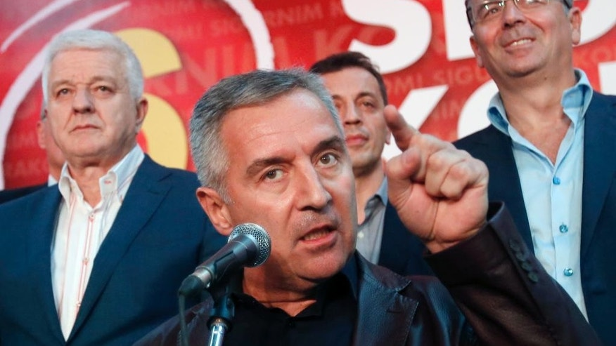 FILE - A Monday, Oct. 17, 2016 file photo of Montenegro's Prime Minister and long-ruling Democratic Party of Socialists leader Milo Djukanovic, center, speaking in his party headquarters, in Podgorica, Montenegro. Russian nationalists were behind an alleged coup attempt and wanting to kill its pro-Western prime minister because of his government's bid to join NATO, the Balkan country's chief special prosecutor said Sunday, Nov. 6, 2016. (AP Photo/Darko Vojinovic, File)