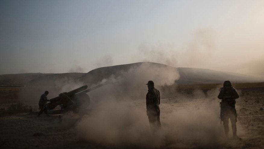 Kurdish Peshmerga soldiers fire artillery at Islamic State positions in Bashiqa, east of Mosul, Iraq, Monday, Nov. 7, 2016. Iraqi Kurdish fighters exchanged heavy fire with IS militants early on Monday as they advanced from two directions on a town held by the Islamic State group east of the city of Mosul. (AP Photo/Felipe Dana)