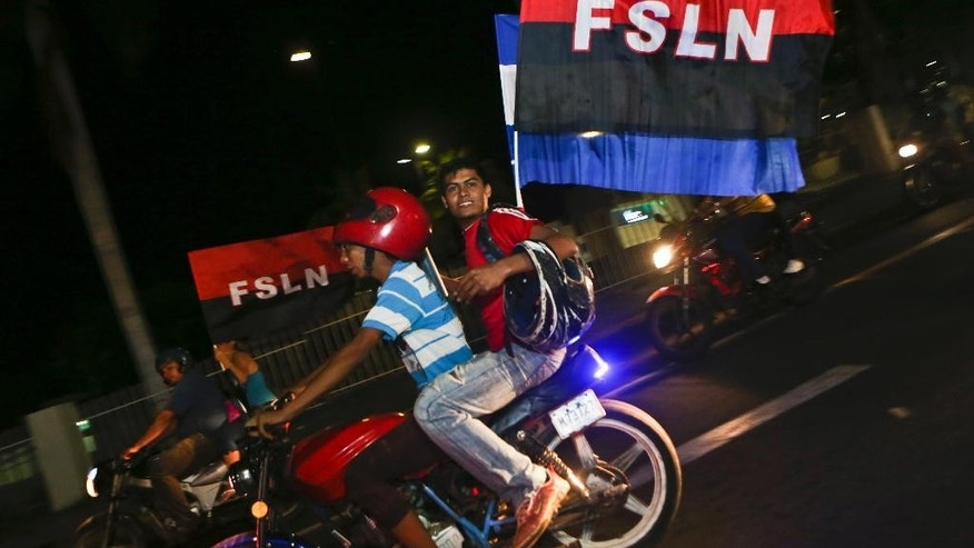 Supporters of Nicaragua's President Daniel Ortega and vice presidential candidate, his wife, Rosario Murillo carry flags of the Sandinista National Liberation Front, or FSLN, as Ortega won re-election, while celebrating in Managua, Nicaragua, Sunday, Nov. 6, 2016. Ortega won a third consecutive term victory in the general election, but critics accused him and his allies of manipulating the political system to guarantee he stays in power by dominating all branches of government. (AP Photo/Esteban Felix)