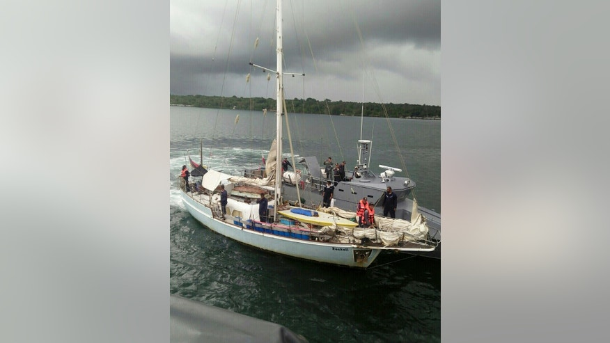"""In this photo provided by the Armed Forces of the Philippines Western Mindanao Command (WESMINCOM) and authorized for distribution by Army Maj. Filemon Tan Jr. Monday, Nov. 7, 2016, Philippine Navy board the yacht marked """"Rockall"""" after being found abandoned off the Sulu Sea in southern Philippines over the weekend. The Philippine military is verifying a claim by Abu Sayyaf militants that they have kidnapped a German man from the yacht and shot and killed his female companion, whose suspected body was found on the abandoned boat, military officials said Monday. Regional military spokesman Maj. Filemon Tan said Abu Sayyaf spokesman Muamar Askali had claimed the militants kidnapped Juegen Kantner and killed his companion while the couple were cruising off neighboring Malaysia's Sabah state. (WESMINCOM via AP)"""