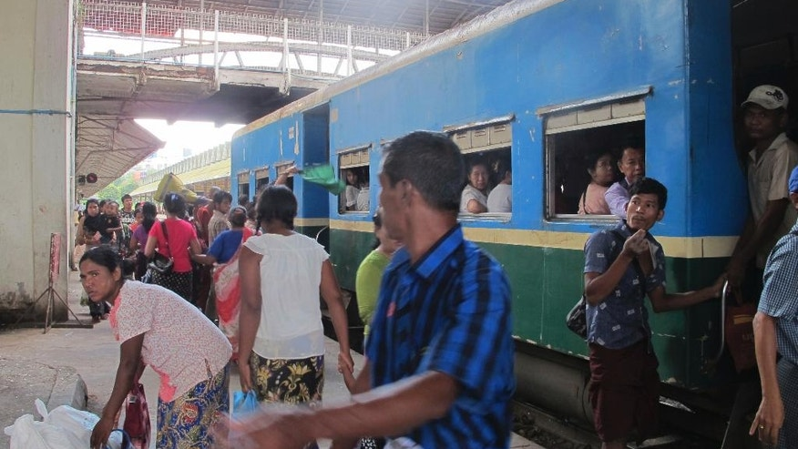 In this Oct. 2, 2016 photo, people get on a Circle Line train at Yangon Central Railway Station in Yangon, Myanmar. Myanmar's commercial capital is fast shedding its sleepy backwater trappings as the city builds new roads, hotels and office buildings. But Yangon's Circle Line railway is a world apart from the traffic jams and chaos of the city's streets. (AP Photo/Elaine Kurtenbach)
