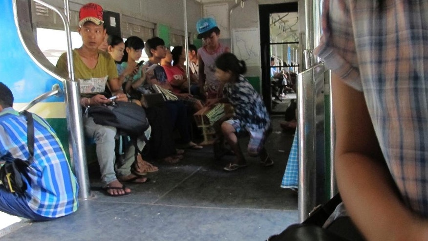 In this Oct. 2, 2016 photo, a girl kneels down and sells bird houses to passengers on a Circle Line train in Myanmar. Myanmar's commercial capital is fast shedding its sleepy backwater trappings as the city builds new roads, hotels and office buildings. But Yangon's Circle Line railway is a world apart from the traffic jams and chaos of the city's streets. (AP Photo/Elaine Kurtenbach)