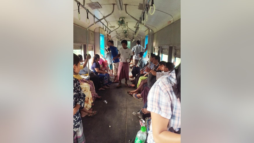 In this  Oct. 2, 2016 photo, a hawker walks among passengers to sell cellphone cards on a Circle Line train in Myanmar. Myanmar's commercial capital is fast shedding its sleepy backwater trappings as the city builds new roads, hotels and office buildings. But Yangon's Circle Line railway is a world apart from the traffic jams and chaos of the city's streets. (AP Photo/Elaine Kurtenbach)