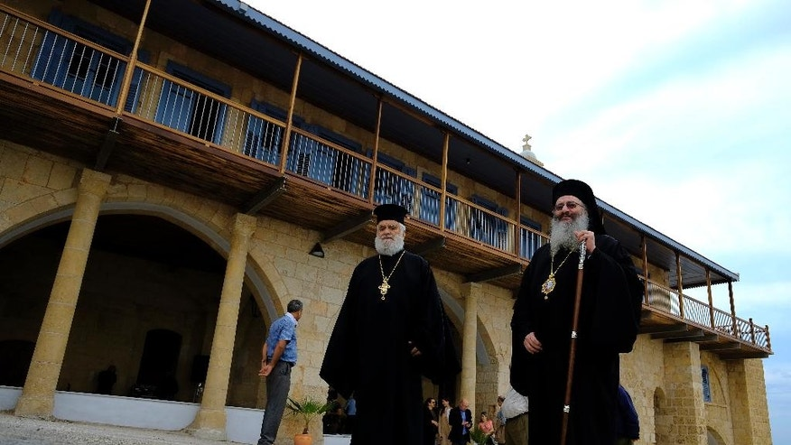 Greek Orthodox priests walk outside of the new restoration Greek Orthodox monastery of Apostolos Andreas in Karpasia in the Turkish Cypriot breakaway northern part of the eastern Mediterranean island of Cyprus, Monday, Nov. 7, 2016. Work carried out jointly by Greek and Turkish Cypriots to restore an Orthodox Christian monastery in ethnically divided Cyprus is being hailed as a symbolic milestone for unity and peace on the eastern Mediterranean island. The monastery is dedicated to one of Jesus' first disciples St. Andrew and has long been revered by both Greek and Turkish Cypriots. (AP Photo/Petros Karadjias)
