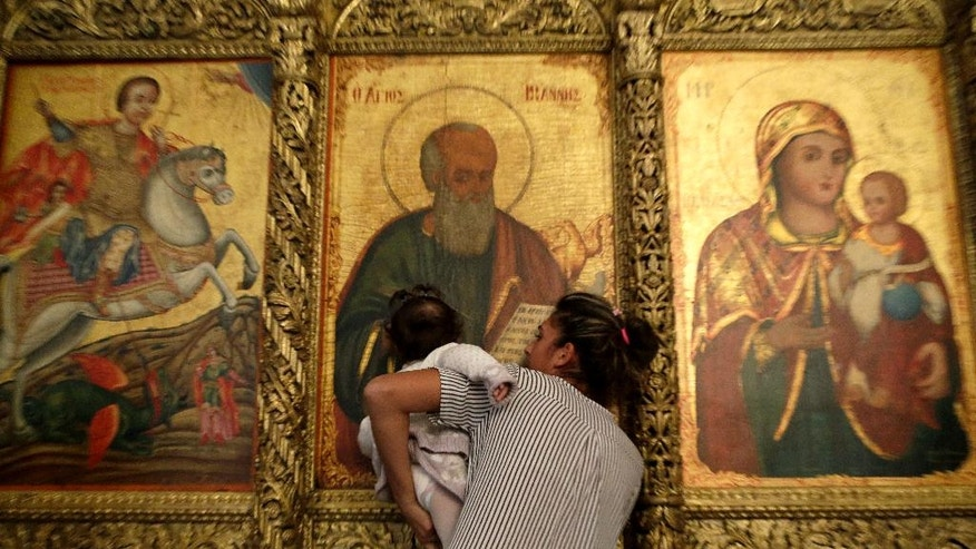 An Orthodox mother with her child kiss the icons as they visit the new restoration Greek Orthodox monastery of Apostolos Andreas in Karpasia in the Turkish Cypriot breakaway northern part of the eastern Mediterranean island of Cyprus, Monday, Nov. 7, 2016. Work carried out jointly by Greek and Turkish Cypriots to restore an Orthodox Christian monastery in ethnically divided Cyprus is being hailed as a symbolic milestone for unity and peace on the eastern Mediterranean island. The monastery is dedicated to one of Jesus' first disciples St. Andrew and has long been revered by both Greek and Turkish Cypriots. (AP Photo/Petros Karadjias)