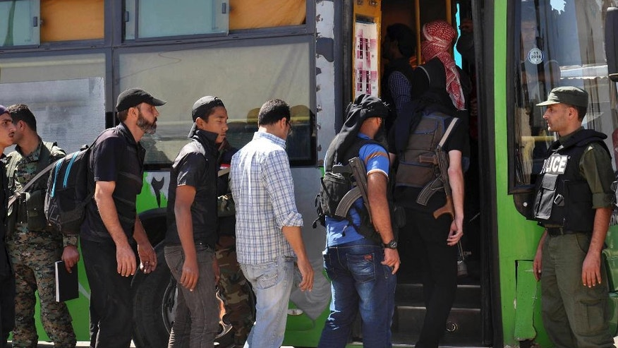 FILE - In this file photo released by the Syrian official news agency SANA on Sept. 26, 2016, anti-Syrian government fighters, left, some of them carrying their weapons, head to a bus as they leave the last besieged rebel-held neighborhood of Al-Waer in Homs province, Syria. The Syrian government has forced thousands of insurgents and their families to relocate to the northern Idlib province as part of truce deals, a move that rebels suspect is aimed at gathering them far from the capital where they can later be eliminated. The al-Qaida stronghold is now home to several insurgent groups, some with radical ideologies, and has been compared to Kandahar, the Taliban's onetime seat of power in Afghanistan. (SANA via AP, File)