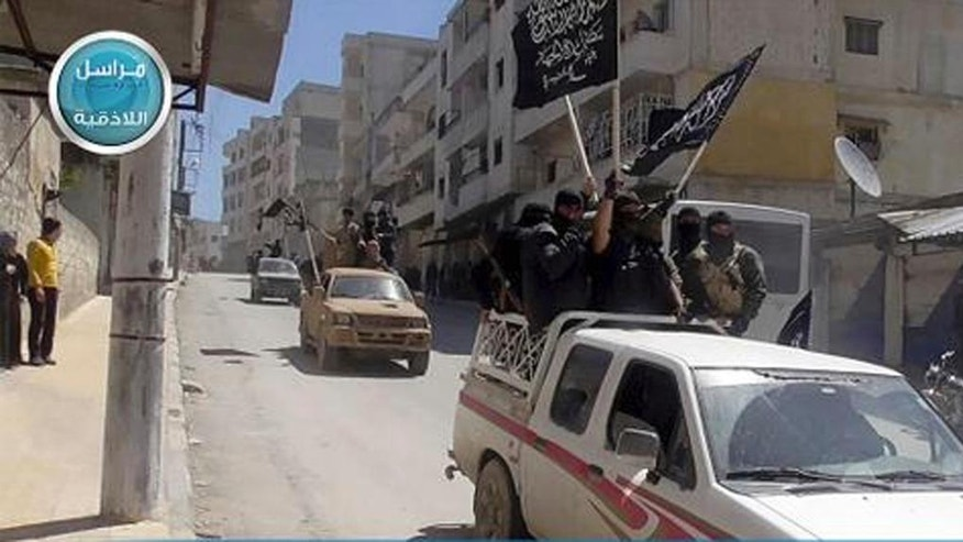 FILE - In this file photo posted on the Twitter page of Syria's al-Qaida-linked Nusra Front on April 25, 2015, which is consistent with AP reporting, Nusra Front fighters stand on their vehicles and wave their group's flags as they tour the streets of Jisr al-Shughour, Idlib province, Syria. The Syrian government has forced thousands of insurgents and their families to relocate to the northern Idlib province as part of truce deals, a move that rebels suspect is aimed at gathering them far from the capital where they can later be eliminated. The al-Qaida stronghold is now home to several insurgent groups, some with radical ideologies, and has been compared to Kandahar, the Taliban's onetime seat of power in Afghanistan. (Al-Nusra Front Twitter page via AP, File)