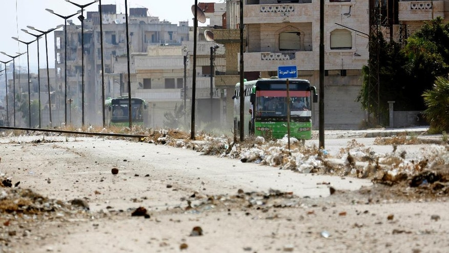 FILE - In this Sept. 22, 2016 file photo, Syrian government buses evacuate residents from Al-Waer, the last rebel-held neighborhood of Homs, Syria. The Syrian government has forced thousands of insurgents and their families to relocate to the northern Idlib province as part of truce deals, a move that rebels suspect is aimed at gathering them far from the capital where they can later be eliminated. The al-Qaida stronghold is now home to several insurgent groups, some with radical ideologies, and has been compared to Kandahar, the Taliban's onetime seat of power in Afghanistan.. (AP Photo, File)