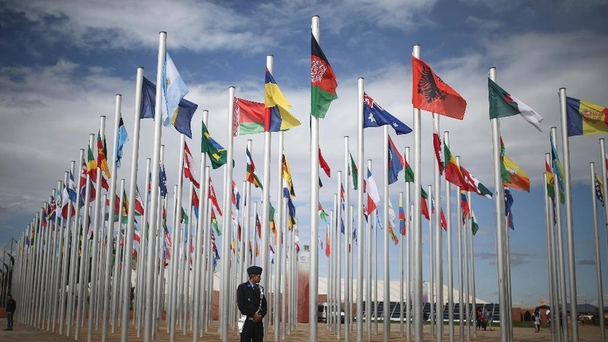 A member of Moroccan security stands guard next to flags of participating UN member states, on the entrance to the COP22 village, a day ahead of the opening ceremony, in Marrakesh, Morocco, Sunday, Nov. 6, 2016. The Climate Conference, known as the COP22, starts Monday in Marrakech. (AP Photo/Mosa'ab Elshamy)