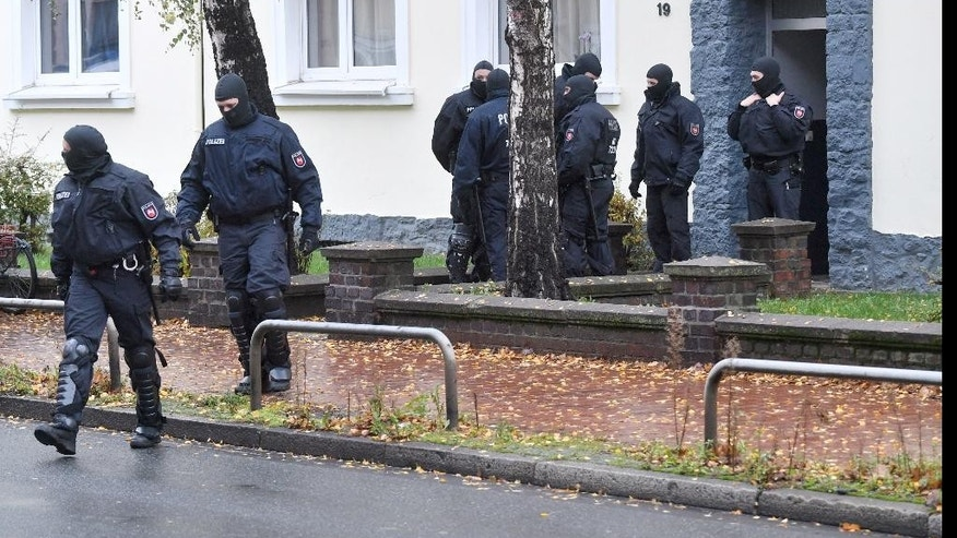 Police officers seach a residential building opposite the German-Speaking Islamic Circle Hildesheim mosque in Hildesheim, Germany, Tuesday, Nov. 8, 2016. German security authorities arrested five men Tuesday on allegations they aided the Islamic State group in Germany, recruiting members and providing financial and logistical help. (Julian Stratenschulte/dpa via AP)
